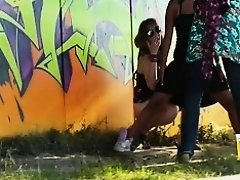 Girl tries to hide her pissing friend from the public